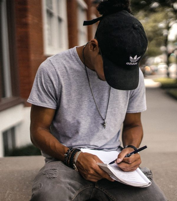 Photo of teen writing in notebook.