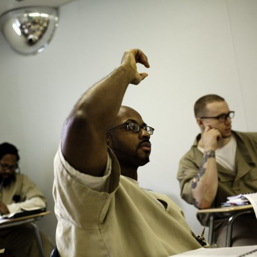 Man in classroom raising hand.