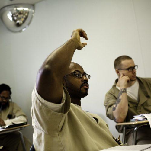 Man in classroom raising hand.