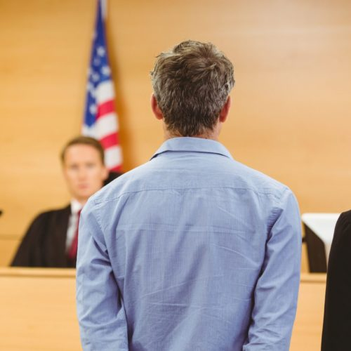 image of judge speaking to lawyer and client in a courtroom