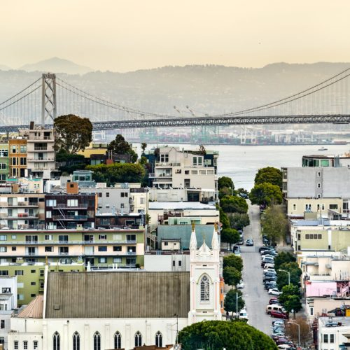 View of the San Francisco - Oakland Bay Bridge and the skyline of the city showcasing various types of housing