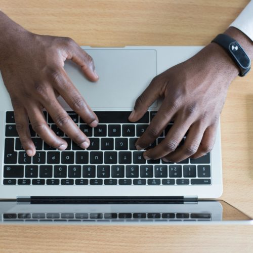 Image of a Black man's hands typing on a laptop. He has on a button down long sleeve shirt.