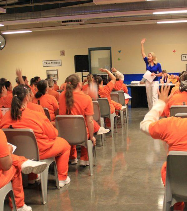 Women in prison listening to motivational speech